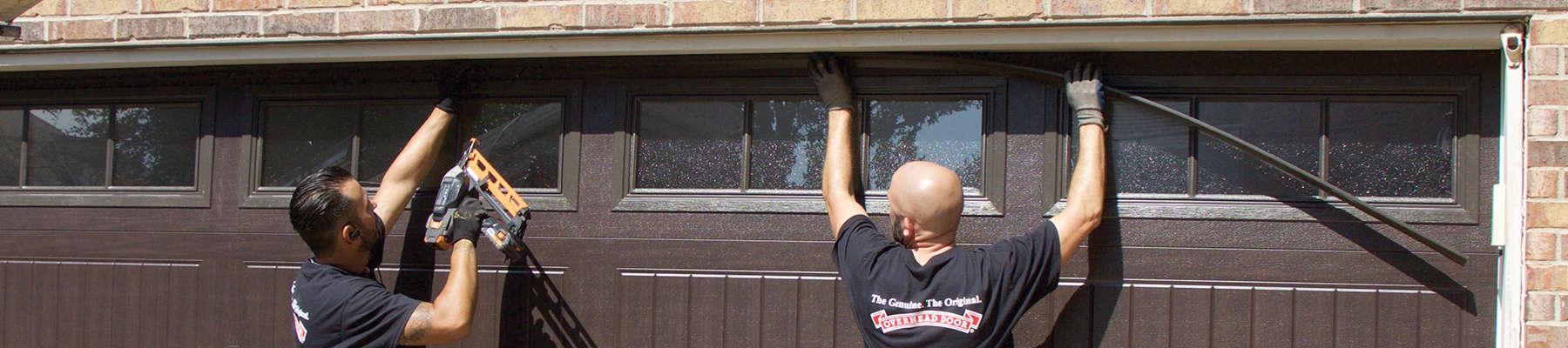 two technicians installing a garage door
